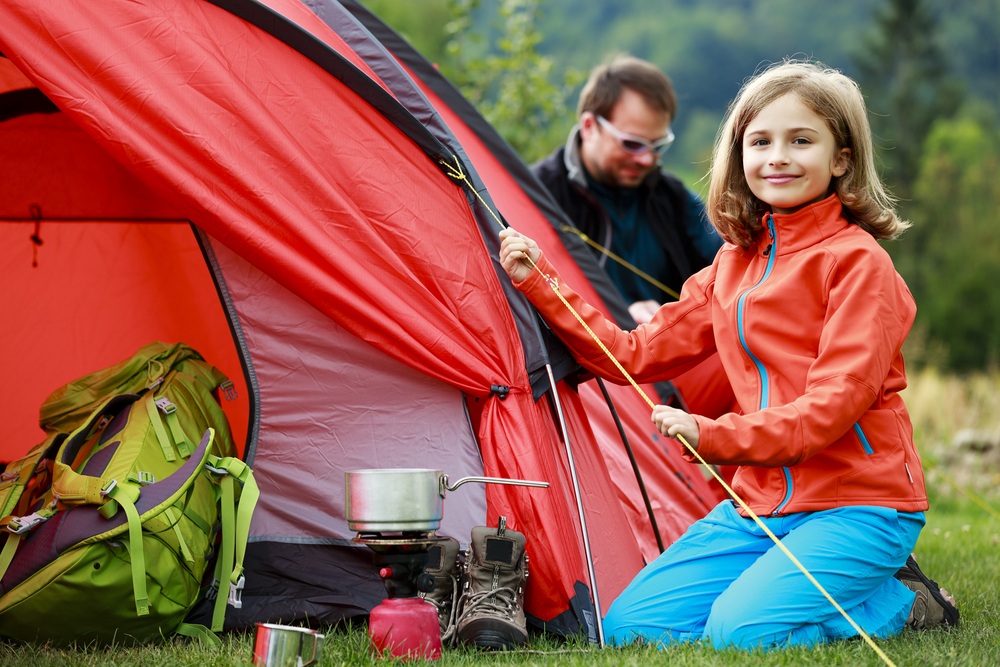 smiling girl next to red family camping tent with dad in background