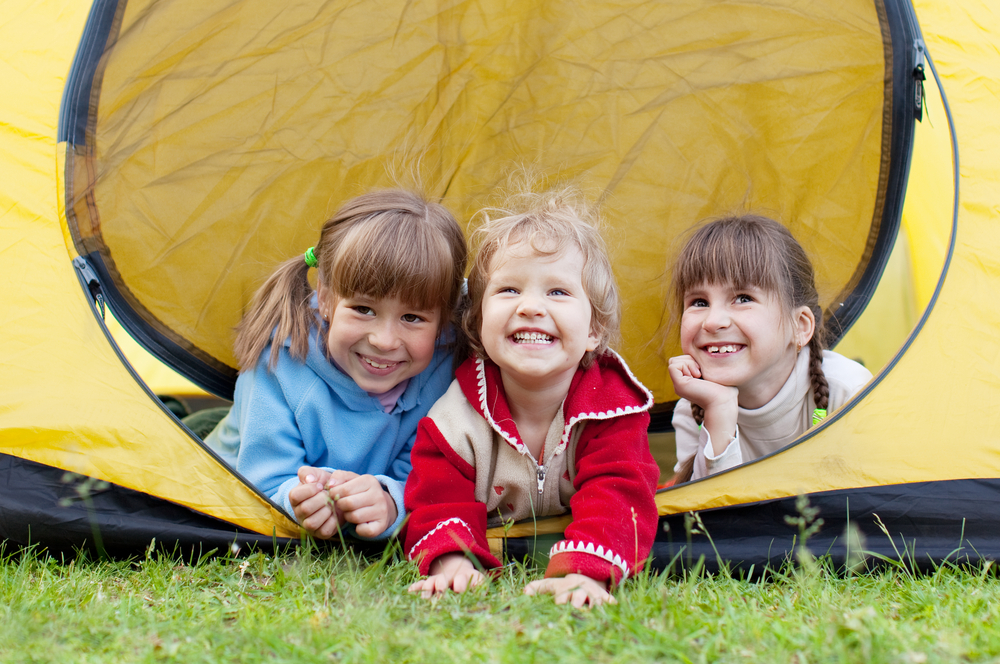 three young children sticking heads out of a yellow tent while on a family camping trip